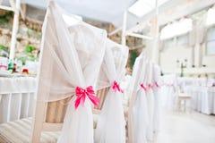 De stoelen van de huwelijksgast met roze linten bij huwelijkszaal Royalty-vrije Stock Foto