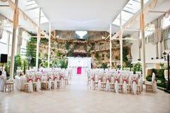 De stoelen van de huwelijksgast met roze linten bij huwelijkszaal Stock Foto's