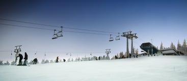 De stoelen van de skilift en skihelling Stock Foto