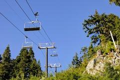 De stoelen van de skilift tegen blauwe hemel Stock Afbeeldingen
