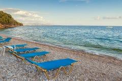 De stoelen van de strandzitkamer in de avond bij de kust van Ionische overzees Stock Afbeelding