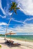 De Stoelen van de strandzitkamer met handdoeken onder paraplu bij de kust van I Stock Afbeeldingen