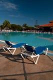 De stoelen van de zon door de pool Stock Afbeelding