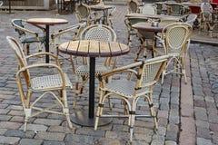 De stoelenlijsten van de straatkoffie aangaande straatstenen Straatkoffie in oude stad - Riga, Letland Stock Foto