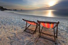 De stoelenstrand en zonsondergang van paren royalty-vrije stock fotografie