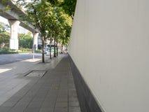 De stoepen met muur en straat in het stadscentrum stock afbeelding