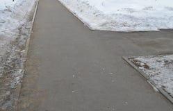 De stoepkruising in het Park, de sneeuw op de kant van de weg, de lenteachtergrond met exemplaarruimte Royalty-vrije Stock Fotografie