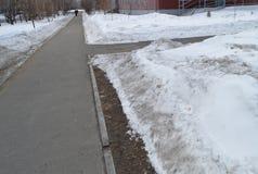 De stoepkruising in het Park, de sneeuw op de kant van de weg, de lenteachtergrond met exemplaarruimte Stock Afbeelding