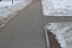 De stoepkruising in het Park, de sneeuw op de kant van de weg, de lenteachtergrond met exemplaarruimte Stock Foto's