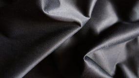 De Stoffenachtergrond van de close-up Zwarte Zijdeachtige Doek met Krommen royalty-vrije stock fotografie