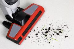 De stofzuiger maakt de grond en het vuil van de vloer schoon Stock Foto