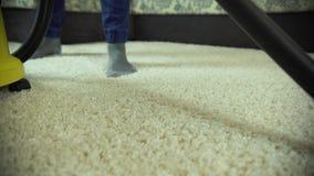 De stofzuiger maakt het tapijt schoon Een mens van een schoonmakend bedrijf werkt, zuigend het tapijt stock video