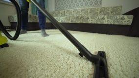 De stofzuiger maakt het tapijt schoon Een mens van een schoonmakend bedrijf werkt, zuigend het tapijt stock footage