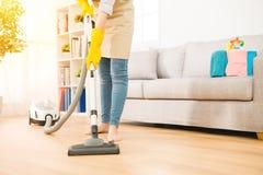 De stofzuiger van het vrouwengebruik aan het schoonmaken Stock Foto