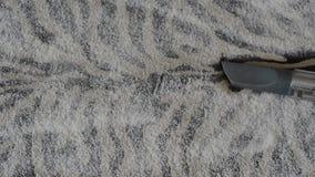 De stofzuiger zuigt het stof van het tapijt tijdens het schoonmaken stock footage