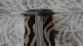 De stofzuiger zuigt het stof van het tapijt tijdens het schoonmaken stock videobeelden