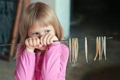 De stok van de meisjesholding met kunstmatige sardines bij museum Stock Foto's