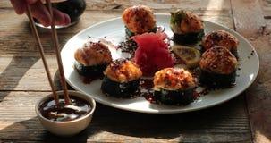 De stokken voor sushi nemen gebakken broodjes en wasabi het onderdompelen uit in sojasaus stock videobeelden