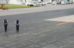 De stokvoering van het luchthavenpersoneel als vliegtuigbladeren, de luchthaven van Naha, Okinawa, Japan stock afbeeldingen
