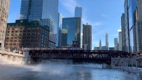 De stoom die van de Rivier van Chicago als temperaturen toenemen werpt zich en opgeheven 'Gr 'leidt kruisen op een brug stock video