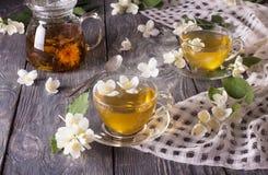 De stoom meer dan Kop van hete thee met Jasmijn, bloemen is verspreid op grijze oppervlakte stock foto