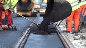 De stoomwalsarbeiders leggen asfaltweg en spoorlijnen aan stock video