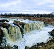 De stora Sioux River flödena över vaggar i Sioux Falls South Dakota med sikter av djurliv, fördärvar, parkerar banor, drevspårbro royaltyfri fotografi