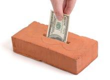 De storting van de Dollar van de V.S. in een de bouwbaksteen Stock Foto's