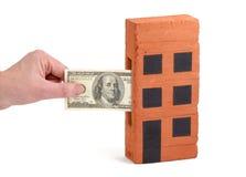 De storting van de Dollar van de V.S. in een huis-baksteen Royalty-vrije Stock Foto's