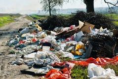 De stortplaats van het huisvuil op de weg Stock Foto's