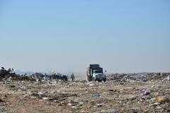 De stortplaats van het stadshuisvuil en de oude vuilnisauto stock foto