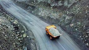 De stortplaatsvrachtwagen is bij steengroeve Hoogste mening van het drijven van oranje stortplaatsvrachtwagen met puin op weg ope stock footage