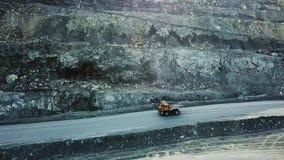 De stortplaatsvrachtwagen is bij steengroeve Hoogste mening van het drijven van oranje stortplaatsvrachtwagen met puin op weg ope stock videobeelden