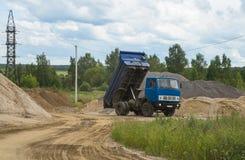 De stortplaatsvrachtwagen maakt bouwzand leeg stock afbeeldingen