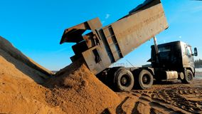 De stortplaatsvrachtwagen maakt grond bij bouwwerf leeg De grote drie-as kippersvrachtwagen giet het zand bij steengroevecarrière stock videobeelden
