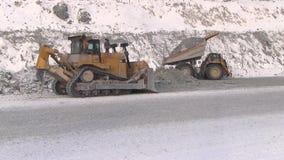 De stortplaatsvrachtwagen maakt stenen van het lichaam naast de tractor leeg stock footage