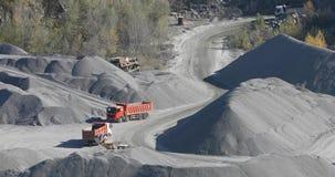 De stortplaatsvrachtwagens berijden in een granietsteengroeve, die steen met zware machines in een steengroeve ontginnen stock videobeelden