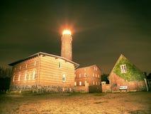 De straal van het vuurtorenzoeklicht door donkere nacht Vuurtoren in Darsser Ort dichtbij Prerow, Stock Fotografie