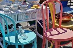 De straat ontbreekt Garage sale Uitstekende Antieke Schotels op Rieten Bureau naast Kleurrijke Houten helder Geschilderde Stoelen Royalty-vrije Stock Foto's