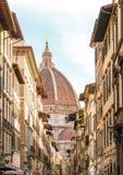 De straat van Florence met oude gebouwen en Santa Maria del Fiore-koepel op horizon Stock Foto's