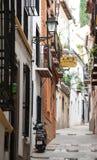 De straat van Granada met een geparkeerde bromfiets Stock Fotografie