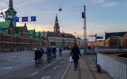 De straat van Kopenhagen met weg, fietsers, mensen en de Beurs van Kopenhagen de oude bouw Borsen op de achtergrond, Denemarken stock afbeelding