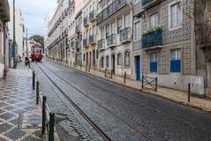 De straat van Lissabon met rode tram Stock Foto