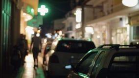 De straat van de nachtstad met geparkeerde auto's en verlichte banners stock videobeelden
