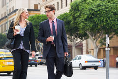 De Straat van zakenmanand businesswoman in met Meeneemkoffie Royalty-vrije Stock Afbeeldingen