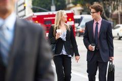 De Straat van zakenmanand businesswoman in met Meeneemkoffie royalty-vrije stock afbeelding