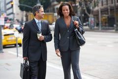 De Straat van zakenmanand businesswoman in met Meeneemkoffie stock foto's