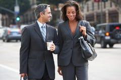 De Straat van zakenmanand businesswoman in met Meeneemkoffie stock afbeeldingen