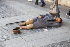 De straatbedelaar ligt stock fotografie