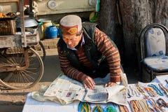 De straathandelaar in oosterse kleding leest de krant royalty-vrije stock foto